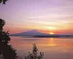Ещё один действующий вулкан Камчатки – Шивелуч, расположен в пределах видимости к северу от Ключевской Сопки. Здесь мы видим восход солнца над вулканом через озеро Куражечное, что неподалёку от посёлка Ключи.