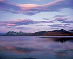 Погружение в ночь. Розовато-сиреневые облака, окрашенные светом уже ушедшего за горизонт солнца, будто стая гигантских птиц распростёрла свои крылья над озером Малык. Парят они, умиротворяя подвластную им территорию, готовят ко сну.